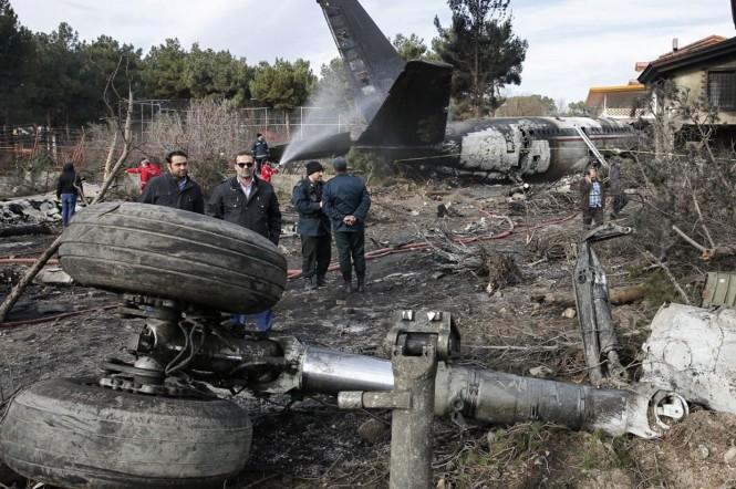 Warga melihat reruntuhan pesawat dalam keadaan terbakar dan asap menggumpal dari lokasi kecelakaan di barat laut Ibu Kota Iran, Teheran, Senin, 14 Januari 2019 waktu setempat. Puing-puing termasuk landing gear dan mesin jet hancur tersebar di dekatnya.