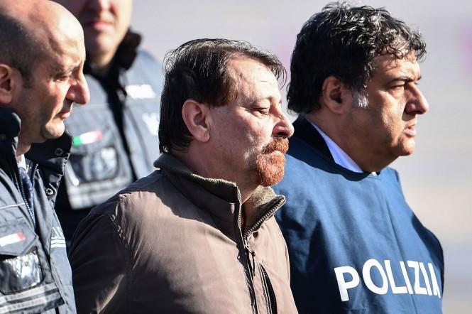 Mantan militan komunis Italia Cesare Battisti (tengah) dikawal petugas kepolisian turun dari pesawat setelah tiba di Bandara Ciampino di Roma, Senin, 14 Januari 2019 waktu setempat.