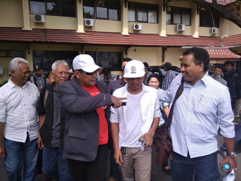 Marzuki 'Kill The DJ' (berbaju dan topi putih) saat melapor ke Polda DIY. Medcom.id-Ahmad Mustaqim