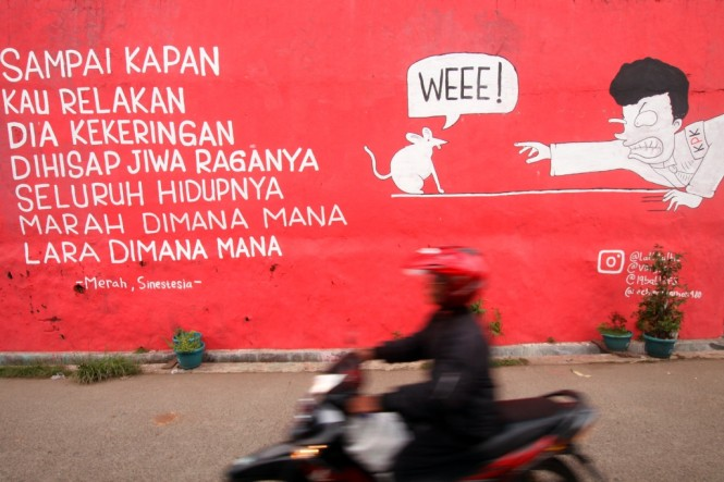Pengendara motor melintasi mural antikorupsi di kawasan Ciputat, Tangerang Selatan, Banten. Foto: MI/Bary Fathahilah.