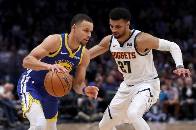 Point guard Golden State Warriors, Steph Curry (kiri), mencoba melewati hadangan guard Denver Nuggets, Jamal Murray (AFP/Matthew Stockman)