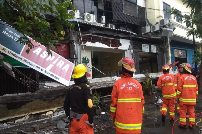 Petugas mengamati tembok ruko di Surabaya yang ambruk akibat terpaan angin kencang, Rabu, 16 Januari 2019, Medcom.id - Hadi