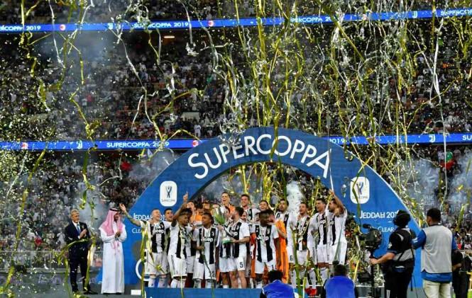 Momen saat para pemain Juventus mengangkat trofi Piala Super Italia 2018 (Foto: AFP/Giuseppe Cacace)