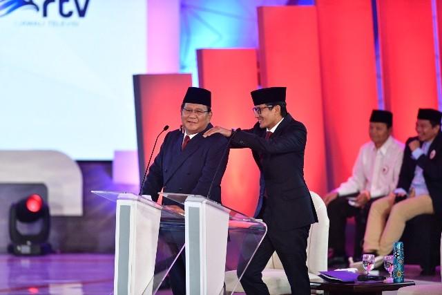 Capres nomor urut 02 Prabowo Subianto (kiri) dipijat pasangan cawapresnya Sandiaga Uno saat jeda Debat Pertama Capres & Cawapres 2019, di Hotel Bidakara, Jakarta, Kamis (17/1/2019).