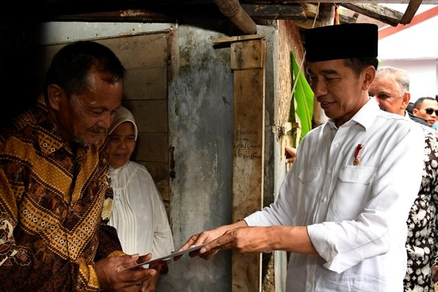 Presiden Joko Widodo (kanan) berbincang dengan penerima fasilitas pemasangan listrik gratis di Kampung Pasar Kolot, Garut, Jawa Barat, Jumat (18/1/2019).  Antara/PUSPA PERWITASARI