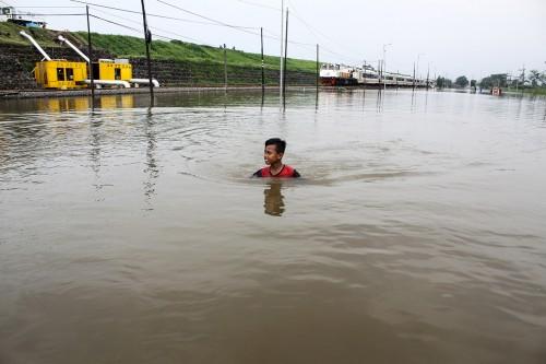 Kereta api melaju di samping Jalan Raya Porong yang terendam