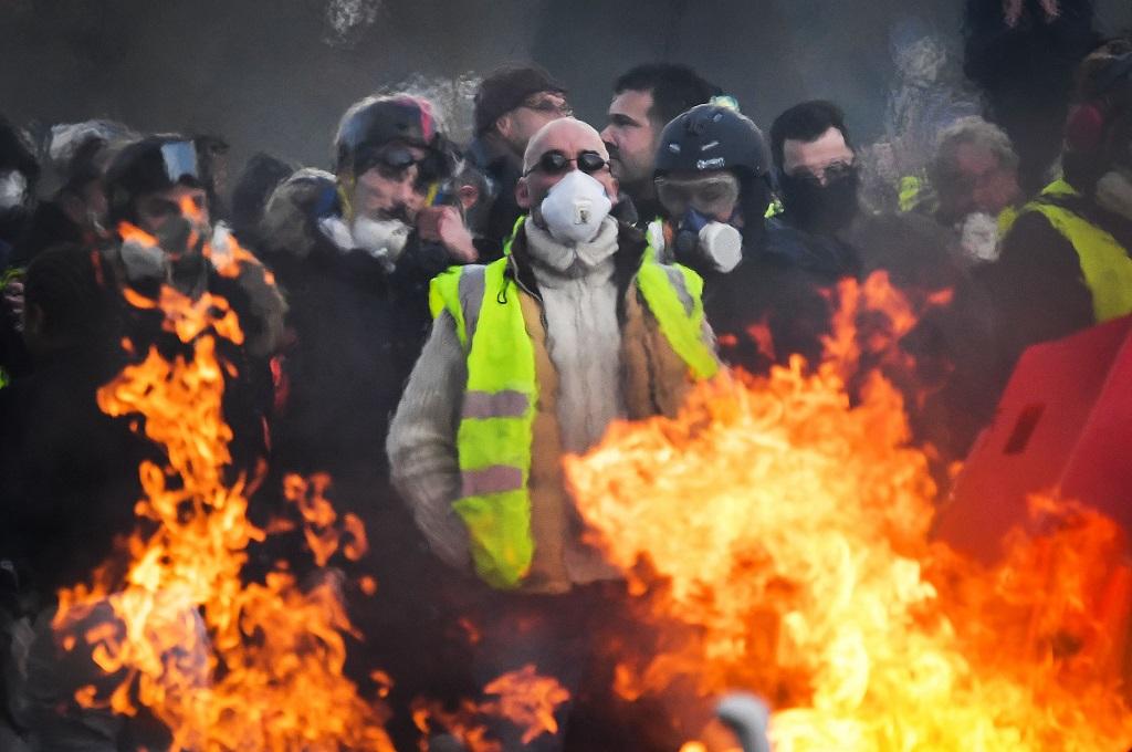 Demonstran rompi kuning berdiri di balik barikade terbakar di Angers, Prancis, 19 Januari 2019. (Foto: AFP/LOIC VENANCE)