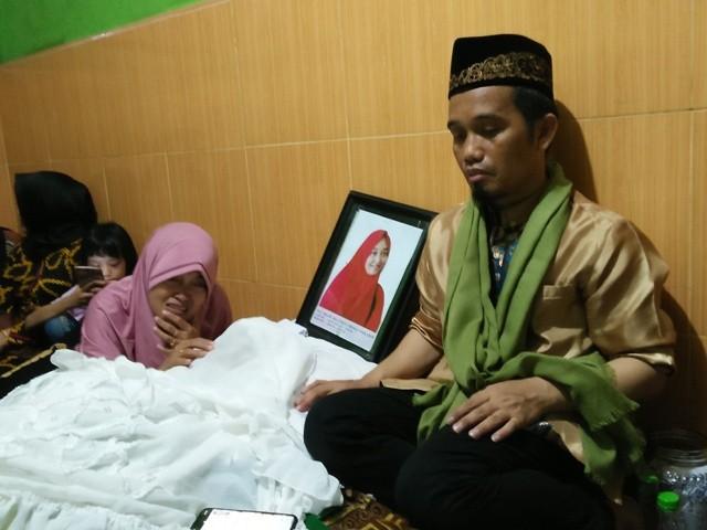 Ustaz Muhammad Nur Mualana di samping jenazah sang istri, Nur Aliyah Ibnu Hajar. Foto: Muhammad Syawaluddin/Medcom.id