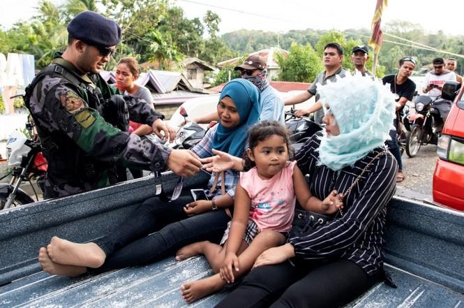 Petugas keamanan memeriksa kartu identitas diri warga di Cotabato Mindanao, Filipina, Minggu 20 Januari 2019, satu hari sebelum referendum wilayah otonomi. (Foto: AFP/NOEL CELIS)