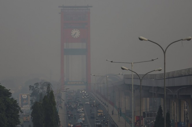 Sejumlah kendaraan melintas di atas jembatan ampera yang diselimuti kabut asap di Palembang, Sumatra Selatan, Minggu (16/9). ANTARA FOTO/Nova Wahyudi.
