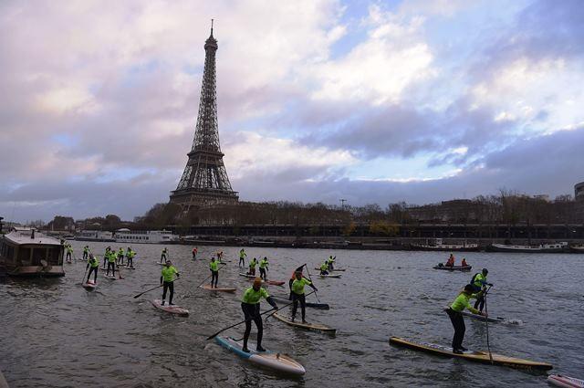 Menara Eiffel di latar para peserta Nautic Paddle Race beradu cepat mendayung papan selancarnya menyusuri Sungai Seine sepanjang 11 kilometer pada 9 Desember 2018. AFP Photo/Lucas Barioulet