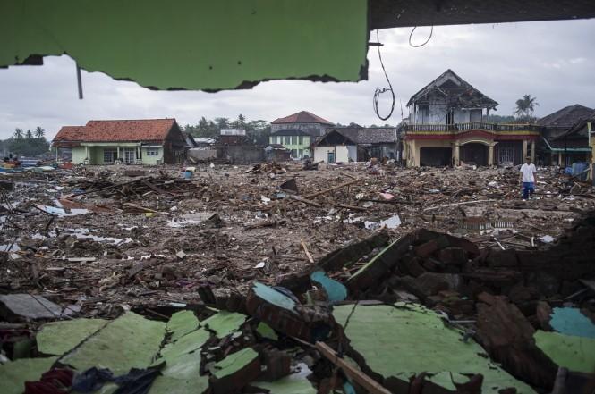 Warga berjalan di sisa-sisa bangunan yang rusak diterjang tsunami Selat Sunda di Sumur, Pandeglang, Banten, Kamis 3 Januari 2019. (Foto: Antara/SIGID KURNIAWAN)