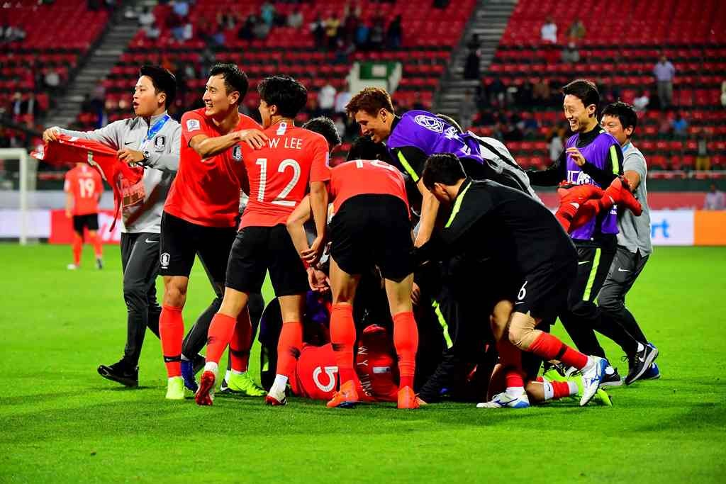 Pemain dan ofisial Korea Selatan merayakan kemenangan atas Bahrain (AFP/Giuseppe Cacace)