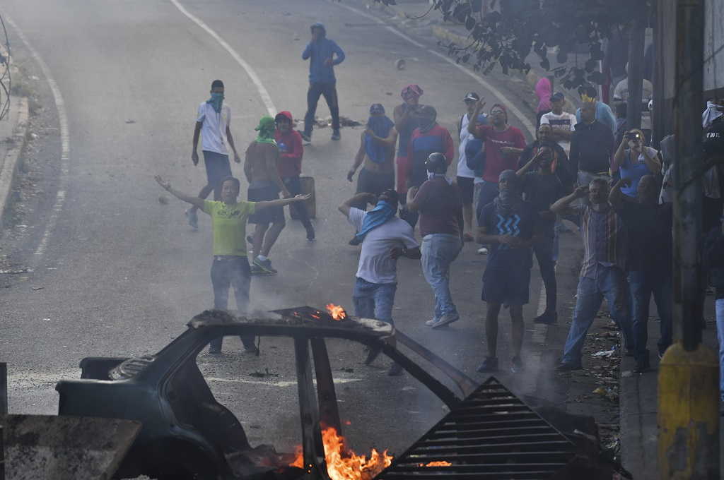 Aksi unjuk rasa berujung bentrok terjadi di Caracas, Venezuela, 21 Januari 2019. (Foto: AFP/YURI CORTEZ)