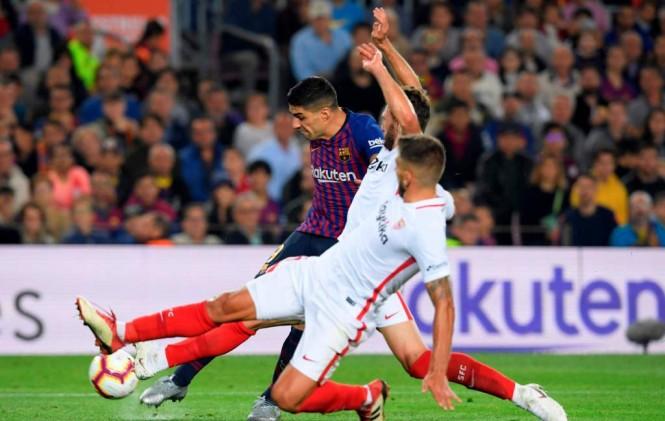 Momen saat Luis Suarez melewati adangan para pemain Sevilla (Foto: AFP/Lluis Gene)
