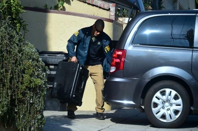 Seorang agen FBI membawa sebuah koper dari sebuah rumah di Los Angeles, AS, 7 November 2018. (Foto: AFP/FREDERIC J. BROWN)