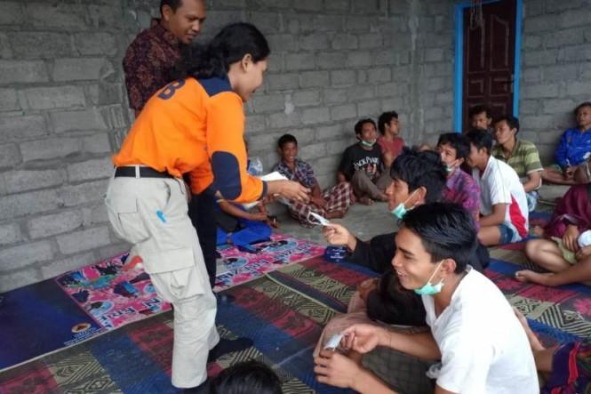 Petugas dari BPBD Karangasem, Bali menyerahkan bantuan masker kepada masyarakat Desa Ban, Kecamatan Kubu guna mengurangi dampak abu vulkanik erupsi Gunung Agung. MEDIA INDONESIA Koresponden, Fotografer: RUTA SURYANA.