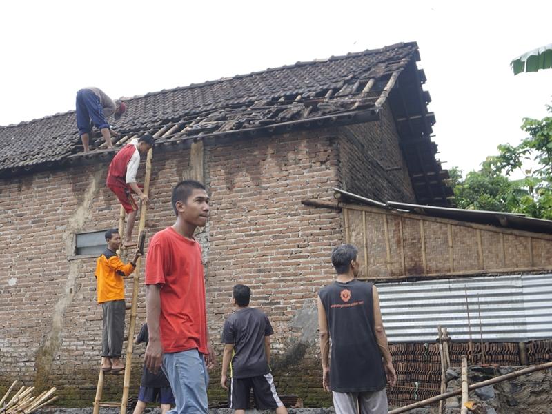 Warga merapikan genting yang berserakan di atap rumah. Medcom.id/Rhobi Shani