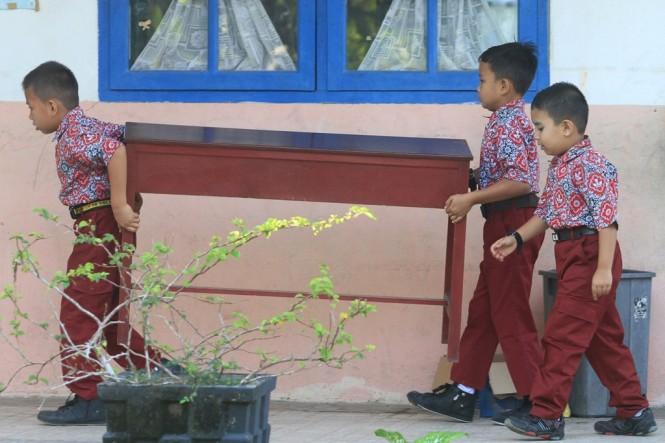 Ilustrasi--Siswa mengangkat meja belajar saat hari pertama sekolah setelah liburan natal dan tahun baru di Sekolah Dasar Negeri (SDN) Suak Timah, Samatiga, Aceh Barat, Aceh. (Foto: ANTARA/Syifa Yulinnas)