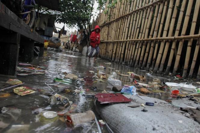 Warga melintasi tumpukan sampah plastik yang terbawa oleh banjir rob kampung nelayan Muara Angke, Jakarta. Foto: MI/Pius Erlangga.