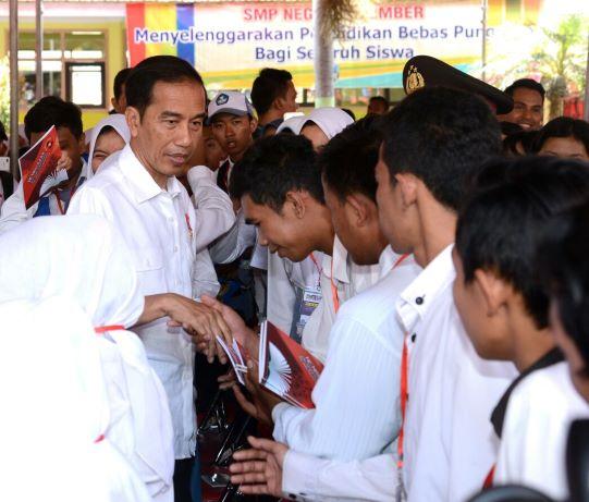 Presiden Joko Widodo sedang menyalami siswa penerima Kartu Indonesia Pintar (KIP) di salah satu sekolah, MI/Agus Mulyawan.
