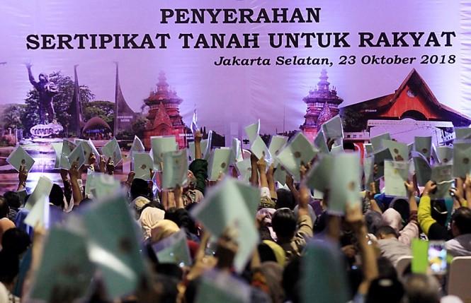 Ilustrasi--Warga menunjukkan sertifikat tanah acara Penyerahan Sertifikat Tanah Untuk Rakyat di Jakarta Selatan. (Foto: MI/Ramdani)