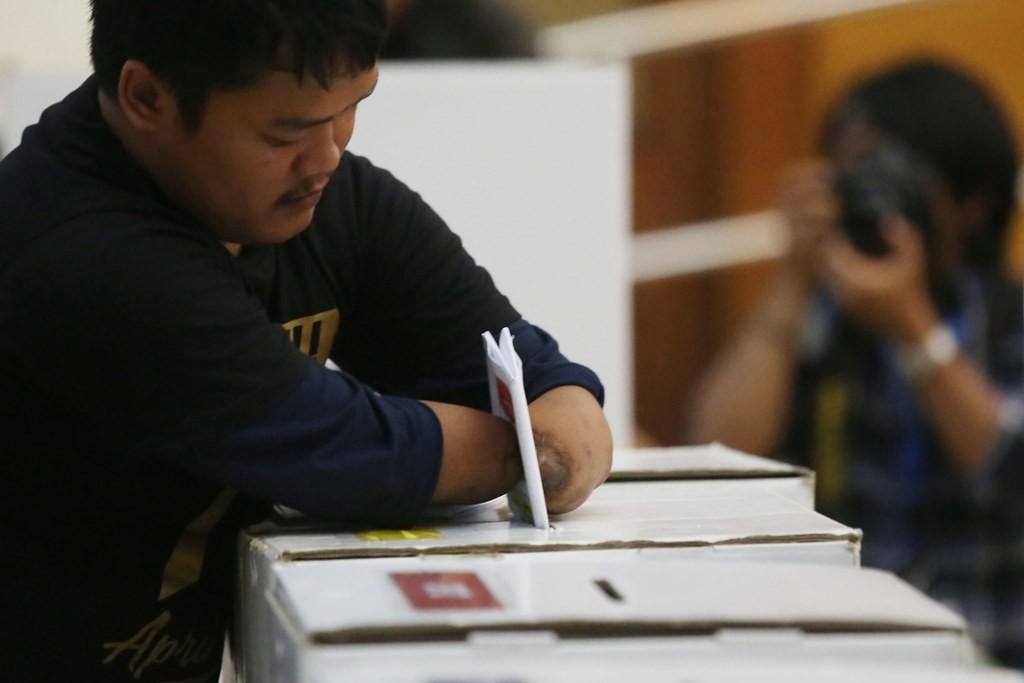 Penyandang disabilitas fisik memasukkan surat suara yang telah dicoblos ke dalam kotak suara saat sosialisasi pendidikan pemilih dan simulasi pemilu 2019 bagi penyandang disabilitas di Jakarta. (Foto: MI/Ramdani)