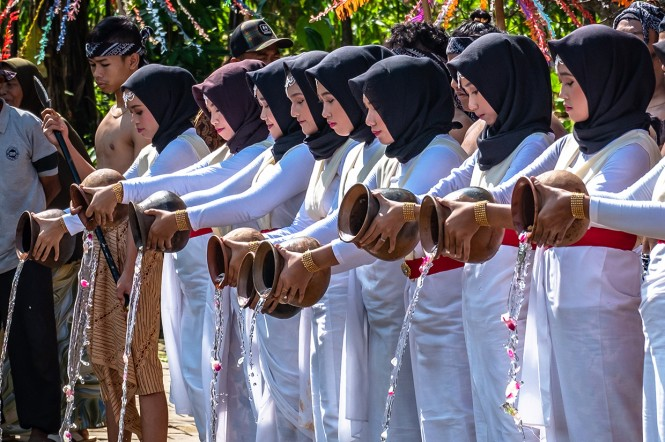 Warga membawa daun pisang saat prosesi kirab Gelar Budaya Nyadran Kali di Desa Wisata Kandri, Gunungpati, Semarang, Jawa Tengah.