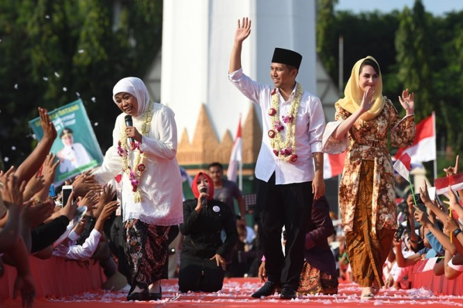 Gubernur Jawa Timur Khofifah Indar Parawansa (kiri) bersama Wakil Gubernur Jawa Timur Emil Elestianto Dardak (tengah) dan istrinya Arumi Bacshin (kanan) menyapa warga ketika tiba di kawasan Tugu Pahlawan, Surabaya, Jawa Timur, Kamis (14/2/2019). ANTARA FO