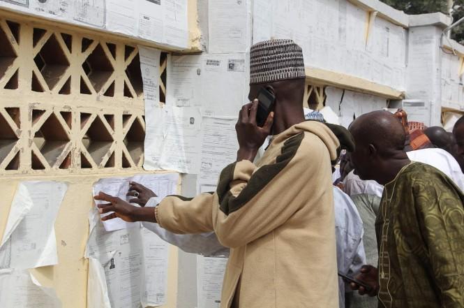 Warga memeriksa nama mereka di daftar pemilih tetap di Maiduguri, Nigeria, 15 Februari 2019. (Foto: AFP/AUDU MARTE)