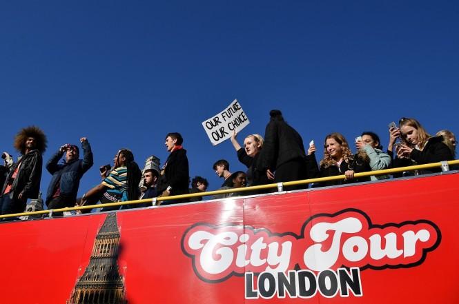 Sekelompok siswa menaiki sebuah bus dalam unjuk rasa isu perubahan iklim di London, Inggris, 15 Februari 2019. (Foto: AFP/BEN STANSALL)