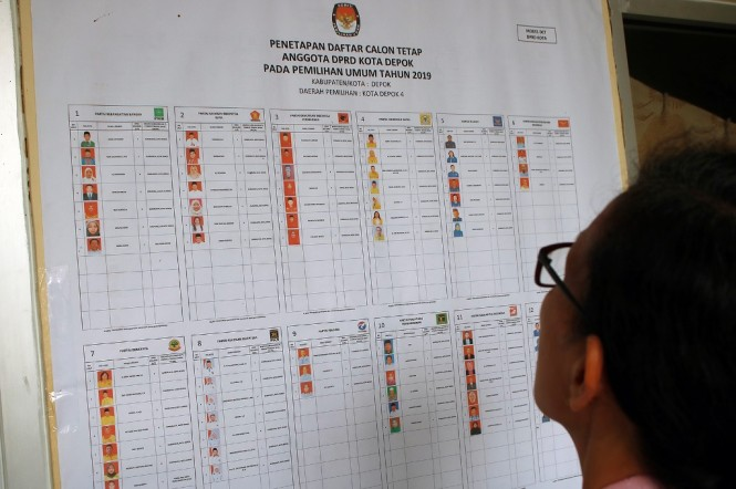 Warga melihat foto penetapan daftar calon tetap anggota DPRD Kota Depok pada Pemilu 2019 di Kelurahan Abadijaya, Depok, Jawa Barat. (Foto: MI/Bary Fathahilah)