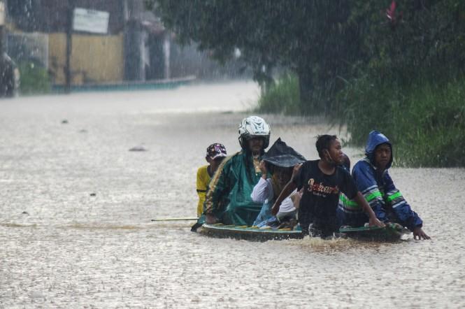 Warga berjalan melintasi banjir yang melanda kawasan Andir, Baleendah, Kabupaten Bandung, Jawa Barat.