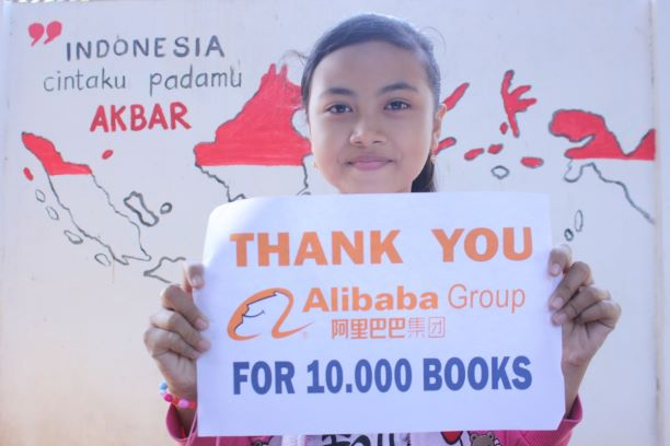 Seorang siswa memegang kertas bertuliskan ucapan terima kasih kepada UCWeb atas donasi 10.000 bukunya.  Foto/Dok UCWeb.