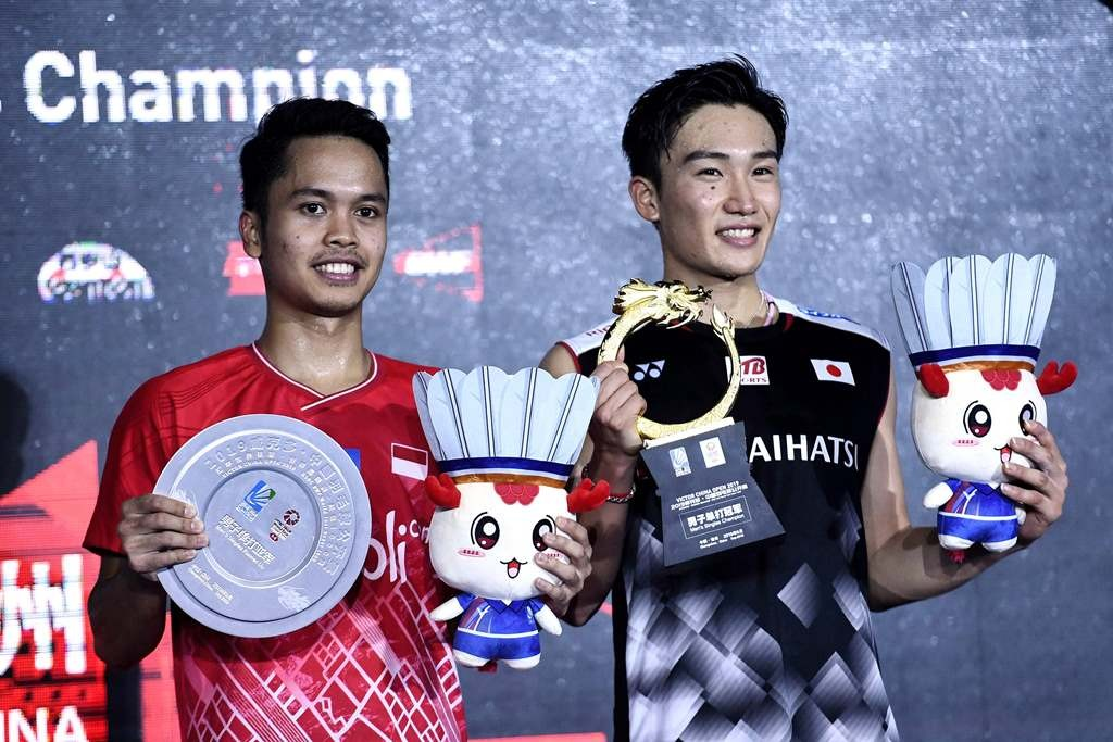 Kento Momota (kanan) dan Anthony Sinisuka Ginting memamerkan trofi China Open 2019). (Photo by STR / AFP)