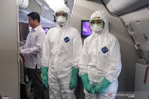 Petugas dengan Pakaian Pengamanan Kesehatan Sambut WNI