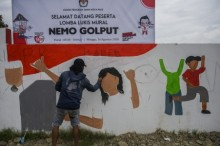 Seorang peserta menyelesaikan lukisannya pada lomba mural bertema Nemo Golput (Jangan Golput) di Palu, Sulawesi Tengah, Minggu, 16 Agustus 2020. Foto: Antara/Basri Marzuki