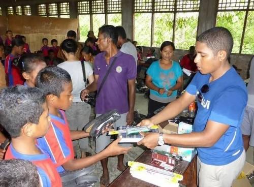 Relawan memberikan sepatu dan alat tulis. (Foto: Shoes for Flores)