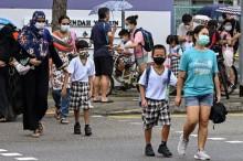 Orang tua menjemput anak mereka dari sebuah sekolah di Singapura, 17 Mei 2021. (Roslan RAHMAN / AFP)