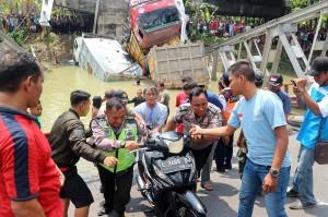 Petugas bersama warga mengevakuasi sepeda motor yang tercebur dalam kejadian runtuhnya jembatan Widang, di Tuban, Jawa Timur.