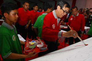 Menkumham Yasonna Laoly (tengah) menggoreskan cat diatas kanvas yang digambar oleh Anak Binaan dalam rangka memperingati hari Bakti Pemasyarakatan Ke- 54 di LP Khusus Anak Tangerang, Tangerang, Banten. ANTARA/Muhammad Iqbal