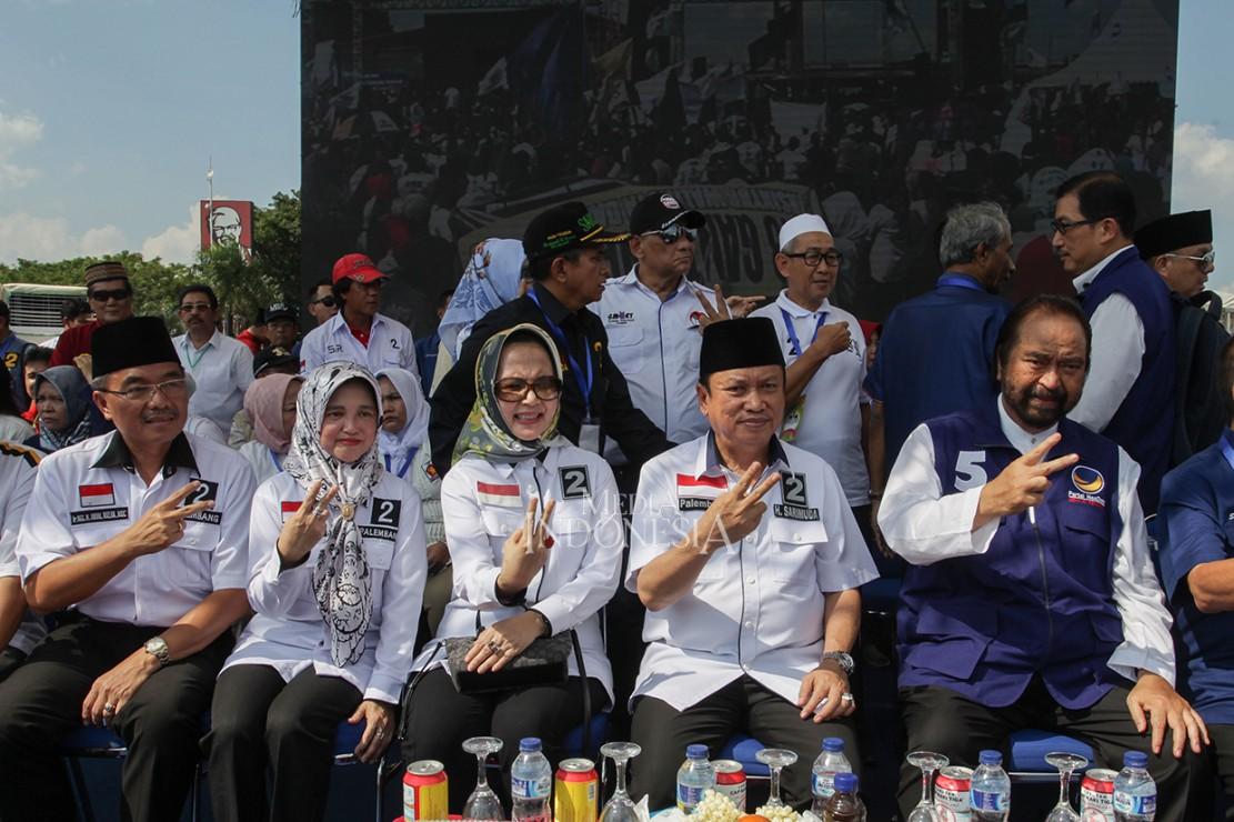 Ketua Umum Partai NasDem Surya Paloh (kanan) berfoto bersama dengan pasangan calon Walikota dan Wakil Walikota Palembang, Sarimuda (kedua kanan) dan Abdul Rozak (kiri) saat kampanye terbuka calon Walikotan dan Wakil Walikota di Benteng Kota Besak, Palembang, Sumatera Selatan.