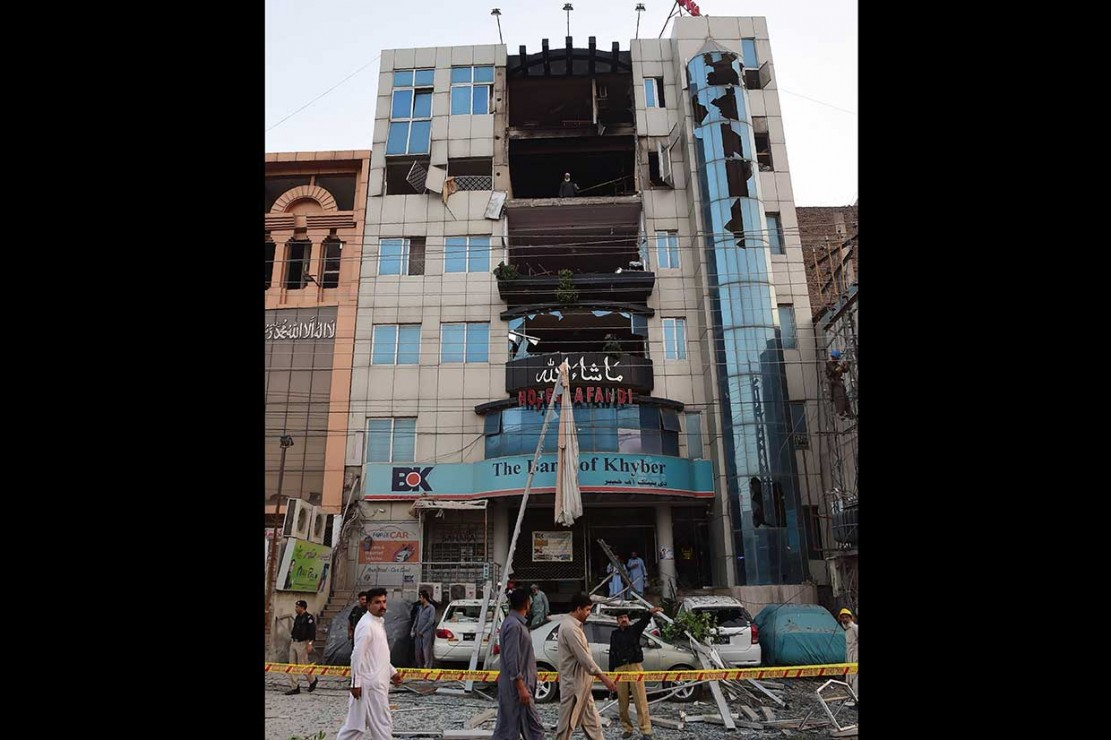 Polisi melakukan penyelidikan terhadap sebuah bangunan hotel yang mengalami kerusakan cukup parah akibat ledakan yang disebabkan kebocoran gas, di Peshawar, Jumat, 11 Mei 2018.