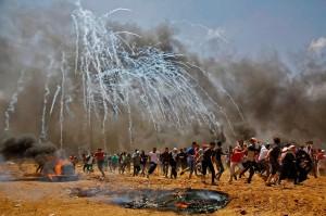 Warga Palestina menyelamatkan diri dari tembakan dan gas air mata yang dilancarkan tentara Israel di Perbatasan Gaza, Senin, 14 Mei 2018.