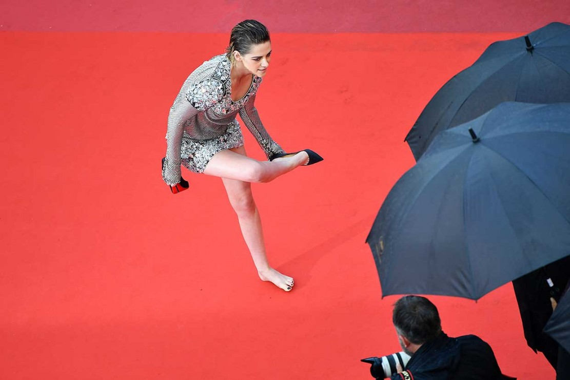 Setelah berfoto untuk wartawan, aktris berusia 28 tahun tersebut secara tidak terduga mencopot sepatunya saat akan menaiki tangga menuju arena teater.