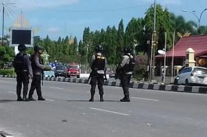 Polisi berjaga di depan Mapolda Riau setelah penyerangan. Medcom.id/Anwar Sadat Guna