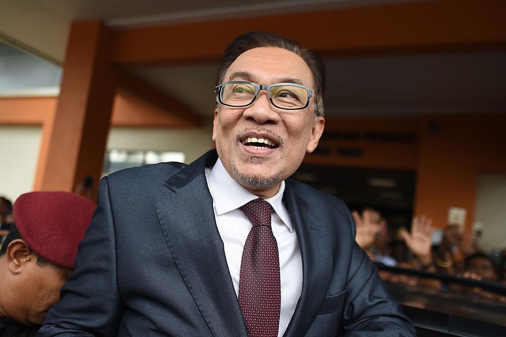 Dengan senyum tersungging di wajahnya dan terlihat elegan dengan setelah hitam, Anwar keluar dari RS Rehabilitasi Cheras, Kuala Lumpur, tempatnya menjalani operasi bahu. AFP/MOHD RASFAN