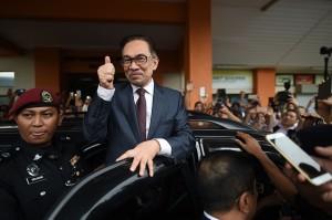 Anwar mengacungkan ibu jarinya ke arah para jurnalis yang menanti sebelum masuk mobil dan melaju tanpa memberikan komentar. AFP/MOHD RASFAN