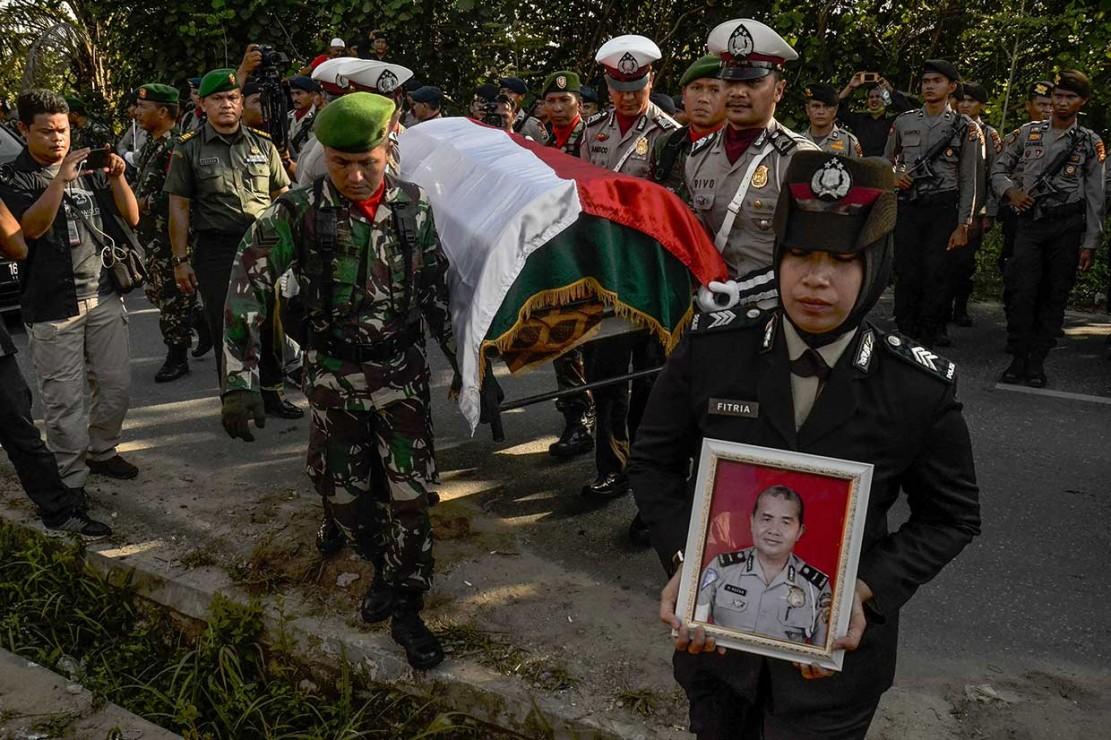 Personel TNI dan Polri mengangkat jenazah Iptu Anumerta Auzar saat upacara pemakaman di Tempat Pemakaman Umum Mayang Sari, Kecamatan Tenayan Raya Kota Pekanbaru, Rabu, 16 Mei 2018. AFP/Wahyudi
