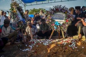 Keluarga berdoa di pusara  almarhum Iptu Anumerta Auzar. Auzar yang bertugas di Direktorat Lalu Lintas Polda Riau meninggal dunia akibat ditabrak mobil pelaku penyerangan di Mapolda Riau. AFP/Wahyudi